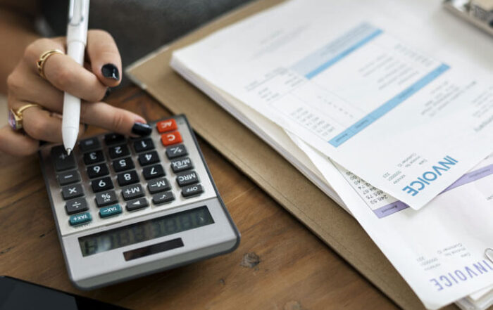 Female Hand Holding Pen Calculating Invoices